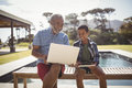 Smiling Grandfather Showing Laptop To Grandson Near Poolside Stock Photography - 97368202