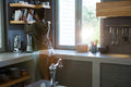 Woman Adjusting Books On Shelf In Kitchen Stock Photos - 97401043
