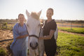 Portrait Of Smiling Jockey And Vet Standing By Horse At Barn Stock Photography - 97408812