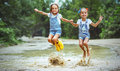 Happy Funny Sisters Twins Child Girl   Jumping On Puddles In Rub Royalty Free Stock Images - 97494129