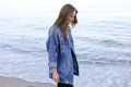 Stylish Woman Steps Confidently Along Seashore And Poses In Came Stock Image - 97513661