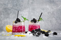 Two Glasses Of Icy Cocktails. Cold Berry Drink. Beverages With Mint, Lemon Citron And Blackberries On A Frozen White Royalty Free Stock Photo - 97530725