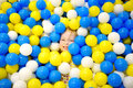 Happy Little Girl Having Fun In Ball Pit In Kids Indoor Play Center. Child Playing With Colorful Balls In Playground Ball Pool. Stock Photo - 97532610
