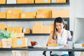 Young Asian Small Business Owner Working At Home Office, Taking Note On Purchase Orders. Online Marketing Packaging Delivery Royalty Free Stock Images - 97626409