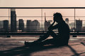 Silhouette Of Sad Depressed Asian Man Lost Hope And Cry, Sit On Building Rooftop At Sunset, Dark Mood Tone Stock Image - 97630641