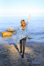 Charming Girl Walks Along Coast And Merrily Fools Around On Sand Royalty Free Stock Images - 97757589