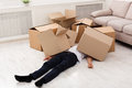 Man Crushed Underneath Cardboard Boxes Stock Photos - 97905683