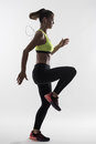 Back Lit Silhouette Of Female Runner In Yellow Tank Top Doing High Knees Exercise Stock Photo - 97915280
