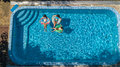 Aerial Top View Of Family In Swimming Pool From Above, Mother And Kids Swim And Have Fun In Water On Family Vacation Royalty Free Stock Images - 97943639