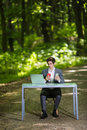 Businessman Sitting At The Office Desk Work At Laptop Computer And Cup Of Coffee Use Mobile Phone On Road Of Green Forest Park. Bu Stock Images - 97969414