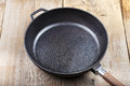 A Cast-iron Frying Pan On A Wooden Background Royalty Free Stock Photo - 97973995