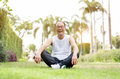 Portrait Of Asian Senior Man Relaxing And Sitting On Grass At Th Stock Photos - 98062093