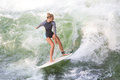 Atractive Sporty Girl Surfing On Famous Artificial River Wave In Englischer Garten, Munich, Germany. Royalty Free Stock Images - 98062519