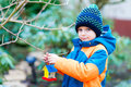Little Kid Boy Hanging Bird House On Tree For Feeding In Winter Stock Photos - 98068303