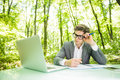 Portrait Of Young Handsome Sad Business Man In Suit Working At Laptop At Office Table In Green Forest Park. Business Concept. Stock Image - 98071191