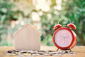 Coins And Wood House With Red Alarm Clock On Table Tree Bokeh Background Stock Images - 98182874