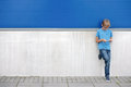 Child With Mobile Phone Standing Near Blue And Grey Wall Outside Stock Image - 98319181