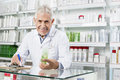 Senior Pharmacist Holding Product While Writing On Clipboard Royalty Free Stock Images - 98346119