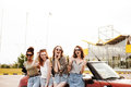 Happy Four Young Women Friends Standing Near Car Outdoors. Stock Photos - 98359913