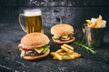 Hamburger With French Fries, Beer On A Burnt, Black Wooden Table. Fast Food Meal. Homemade Hamburger Consist Of Beef Meat, Lettuce Royalty Free Stock Photography - 98364227