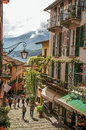 View Of Alley In Hillside, Buildings With Bindweed And Lake Como In Bellagio. Royalty Free Stock Images - 98376529