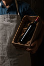 Old Winemaker Holding A Wooden Box With Bottle Of Red Wine Royalty Free Stock Photography - 98377517