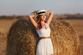 A Beautiful Slender Girl In A White Dress Is Standing Near A Hay Royalty Free Stock Photos - 98397038