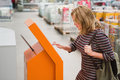 A Woman Chooses The Goods Online At The Self-service Device Stock Photos - 98413763