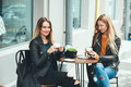 Two Beautiful Attractive Stylish Women Are Sitting Outdoor In Cafe Drinking Coffe And Tea Talking And Enjoying Great Day. Stock Photos - 98438023