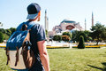 A Traveling Man With A Backpack In Sultanahmet Square Near The Famous Aya Sofia Mosque In Istanbul In Turkey. Travel Stock Image - 98533741