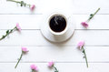 White Cup Of Coffee With Pink Flower On White Wooden Table In The Morning Sunny Day. Stock Image - 98665571