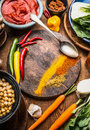 Indian Vegetarian Cooking Ingredients With Colorful Ground Spices , Indian Curry Paste, Chick Peas , Vegetables And Spoon On Wood Royalty Free Stock Photo - 98720425