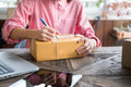 Start Up Small Business Owner Writing Address On Cardboard Box A Stock Photo - 98764420