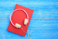 Book And New Modern Pink Music Headphone On Blue Wooden Plank Ba Stock Photos - 98800443