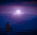 Man Sitting On A Wooden Fence And Enjoy Full Moon Rising Royalty Free Stock Images - 98838999
