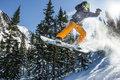 Snowboarder Freerider Jumping From A Snow Ramp In The Sun On A Background Of Forest And Mountains Stock Photos - 98993493