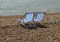 Deckchairs On Pebble Beach Stock Images - 993494