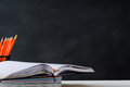 Book And Pencil On White Table Black Board Background Royalty Free Stock Photo - 99060015