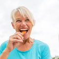 Mature Woman Bites In A Carrot Royalty Free Stock Photography - 99082687
