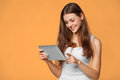 Excited Girl In White Shirt Using Tablet. Smiling Woman With Tablet Pc, Isolated On Orange Background Royalty Free Stock Image - 99145266
