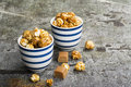 Sweet Caramel Popcorn In Two Ceramic White Striped Blue Bowls On A Stylish Gray Stone Background. Selective Focus. Stock Image - 99153301