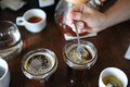 The Process Of Cupping. Tasting Freshly Brewed Coffee With Spoons. Coffee Accessories On The Table Stock Photo - 99233460