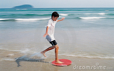 Boy Surfing through waves