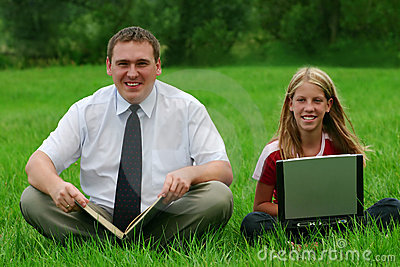 Man and girl sitting on the grass