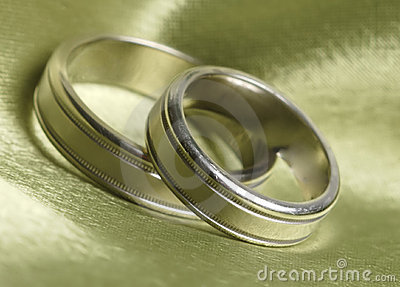 Wedding bands up close on green satin