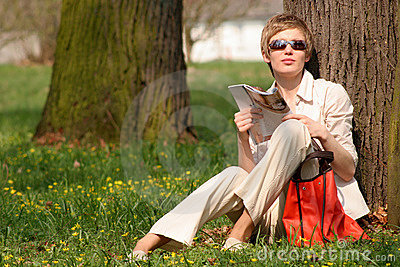 woman with magazine in the park