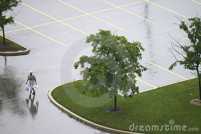 Lone Pedestrian in Empty Wet Parking Lot