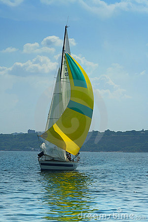 Beautiful yellow sail in the light-blue sky