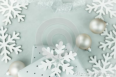 Gift boxes wrapped in silver paper. Curled silver ribbon. Christmas baubles, snow flakes arranged in frame. Copy space for text.