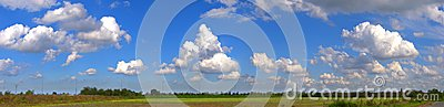 Panoramic landscape with blue sky and puffy clouds